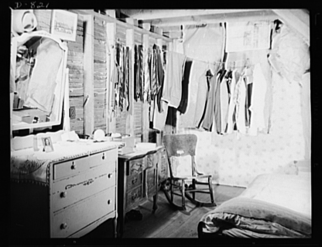 Defense housing, Erie, Pennsylvania. Living conditions were so crowded in Erie, Pennsylvania, that a defense worker and his family of three were found to be living in this attic room. One of the defense industries there, which holds large contracts for the Navy, expects an increase of 4,000 workers during the coming year. Practically all vacancies are already taken, and even the contemplated construction of new homes will fill only a fraction of the need. Realizing the urgency of this need, the Division of Defense Housing has programmed 300 homes in this area, 60 of which are already completed (July 1941). In the meantime, trailers are being used by the Division as a temporary expedient until the more permanent homes are completed