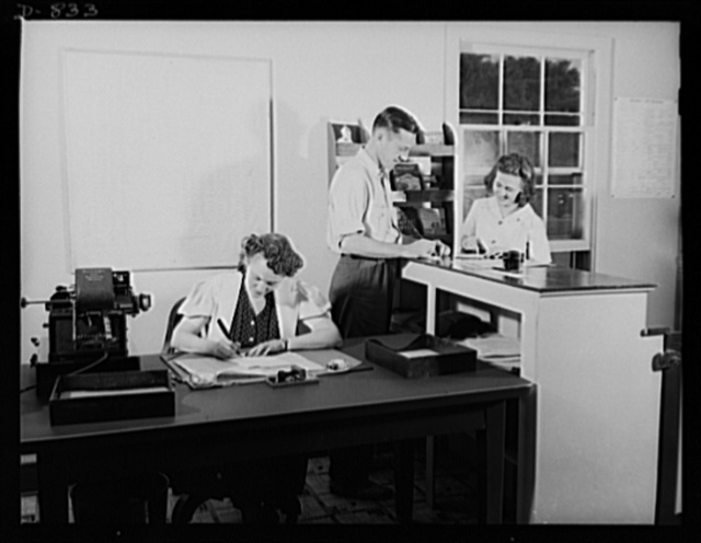 Defense housing, Erie, Pennsylvania. Milton Ackerman, manager of the Defense Trailer Project at Erie Pennsylvania, receives an application from Mrs. George Cole. Her husband is employed in the General Electric plant, which holds large defense contracts. Seated at the desk is Ackerman's assistant, who handles mail, and telephone inquires for tenants