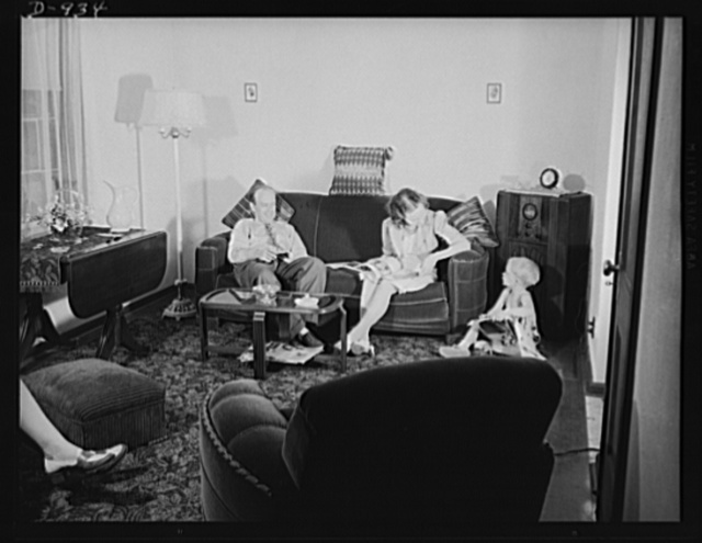 Defense housing, Erie, Pennsylvania. Mr. and Mrs. B.J. Rogan and their small son, Bernie, at home in the living room of their new defense home in Erie, Pennsylvania. Mr. Rogan is a drill press operator at the nearby General Electric Company plant. He earns $42.50 a week, and pays about twenty percent of his income for rent. Before moving into a newly constructed defense home at the Franklin Terrace housing project, he lived in a remodeled attic, and then in a trailer. For the latter he paid 6 dollars a week, including all utilities