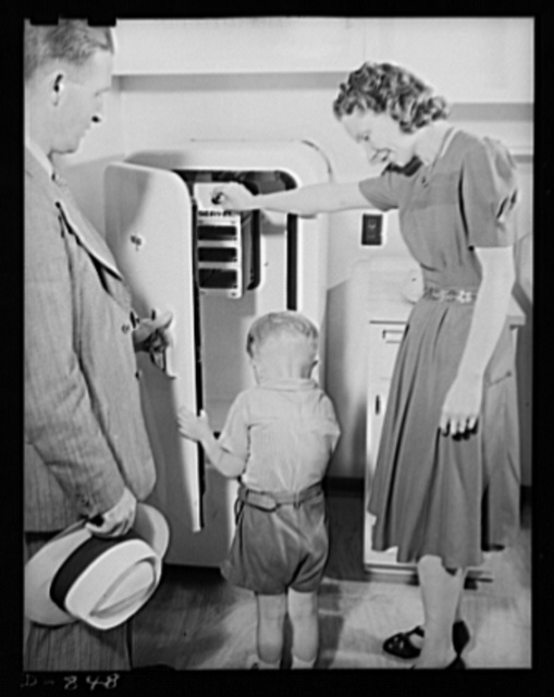 Defense housing, Erie, Pennsylvania. Mrs. B.J. Rogan and young son inspect the gas operated refrigerator of their new defense home, while J.P. Kane, housing manager, looks on