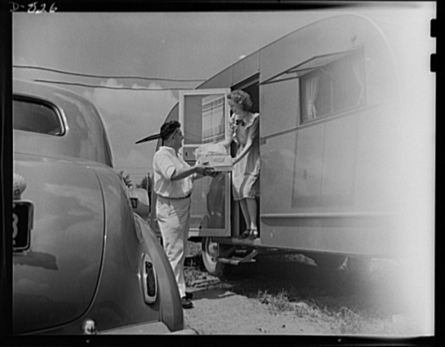 Defense housing, Erie, Pennsylvania. Mrs. B.J. Rogan receives deliveries of laundry, ice and grocery items from local businesses that serve the defense trailer camp twice daily. Mrs. Rogan's husband is employed by the General Electric Company as a drill press operator or defense work. Although grocery stores and milk companies deliver to the doors of the trailer town, agents, salesmen and canvassers are forbidden in the settlement. This is to see that the defense workers on the night shift may sleep during the morning or early afternoon