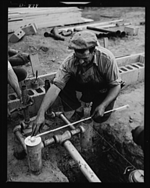 Defense housing, Erie, Pennsylvania. Plumbing that has been assembled at a central shop on the construction site is speedily placed in the foundation of a defense house at the Franklin Terrace housing project