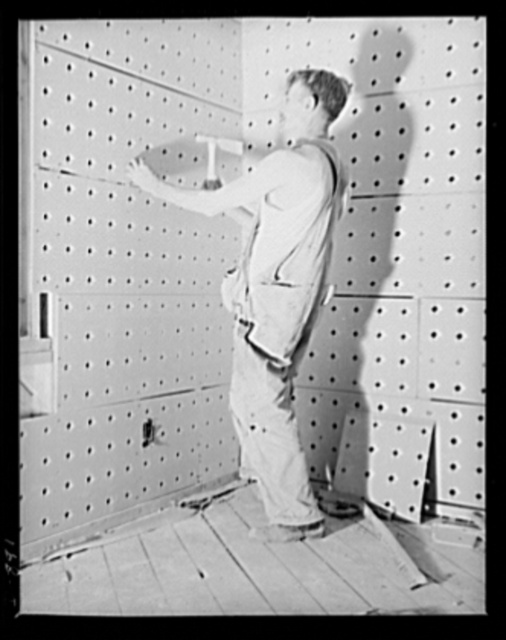Defense housing, Erie, Pennsylvania. Pre-fabricated sheets of asbestos reinforced with gypsum serve as an economical base for plaster walls and ceilings. These sheets, nailed directly to studs, also afford protection against heat and cold. A crew of fourteen men (ten lathers and four laborers) can lathe a four-unit building in a few hours. A crew of plasters moves in as the crew of lathers moves out. Although defense homes are speedily built, they are soundly constructed. Government inspectors keep a rigid check to see that all construction materials live up to government standards