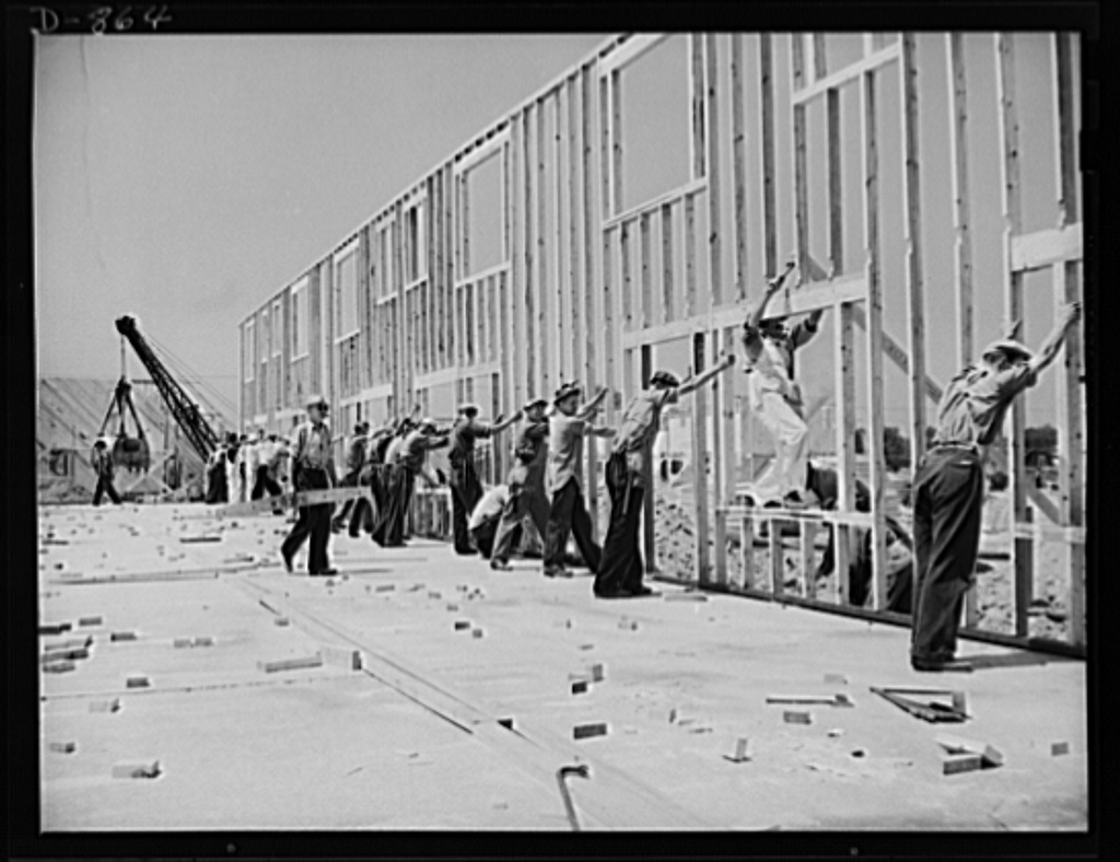 Defense housing, Erie, Pennsylvania. The entire framework, including sections for doors and windows, is fabricated horizontally. The crew working here will later move to another site and repeat the procedure. This circulation of crews who are experienced in one type of construction adds to the speed with which defense homes are being built. Two crews of forty men each are used to raise the stud frames of a four-unit defense home. On the project shown here, one crew started the framework at 8:30am, fabricating it horizontally, and finished it at noon. The other crew moved in shortly after, erected the stud frame, ends, and floor joists, and finished the entire framework by 4:30pm the same day