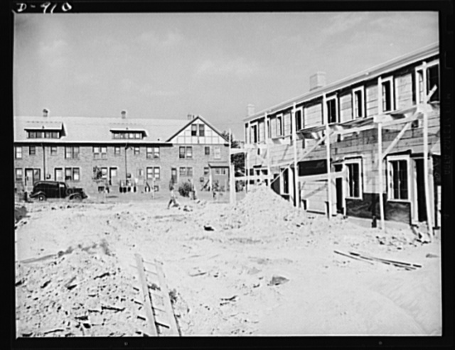 Defense housing, Erie, Pennsylvania. The old and the new. At the right is pictured one of the new defense homes now under construction, while in the background is shown one of the apartment homes built for the defense workers during World War I. Where as many of the latter homes were disposed of due to private concerns after the war, it is expected that many of the new defense homes now being built will eventually become part of the overall slum clearance program. Others will help fill the urgent peace time need in America for low cost homes