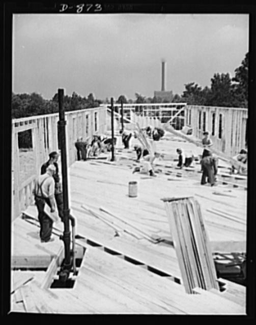 Defense housing, Erie, Pennsylvania. The sheeting-over of the second floor nears completion. Buildings of the plant where are employed many of the defense workers who will move into these homes, can be seen in the background