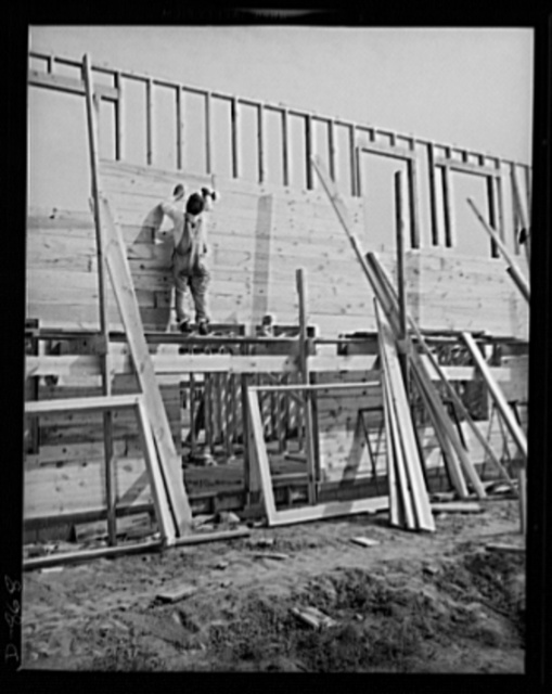 Defense housing, Erie, Pennsylvania. The wall sheeting mounts rapidly. Pre-cut sheeting is always at hand to keep this carpenter supplied, thereby cutting down waste time