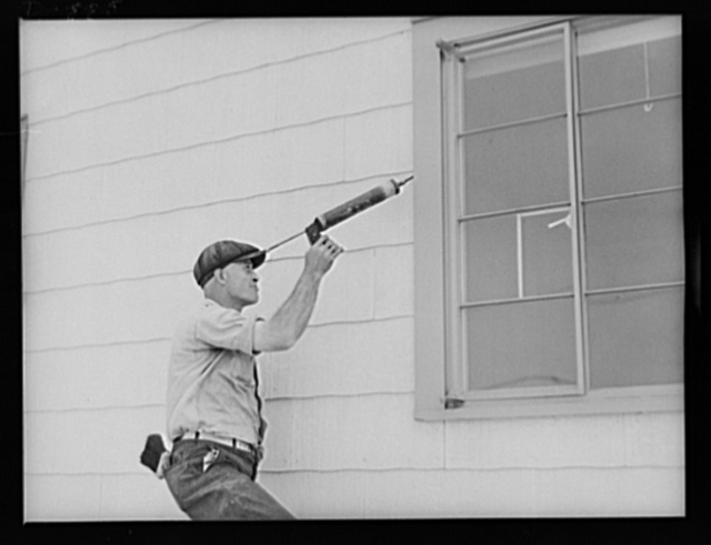 Defense housing, Erie, Pennsylvania. This worker caulks window frames with a pressure gun. Air pressure quickly forces putty into crevices which cannot be reached by hand