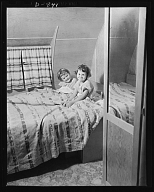 Defense housing, Erie, Pennsylvania. Two of the defense trailer youngsters are tucked in for the night. Their pullman-like bed folds into two seats by day, forming a dining alcove, along with a drop-leaf table. Notice the privacy made possible by two doors, which have dressing mirrors on the opposite side
