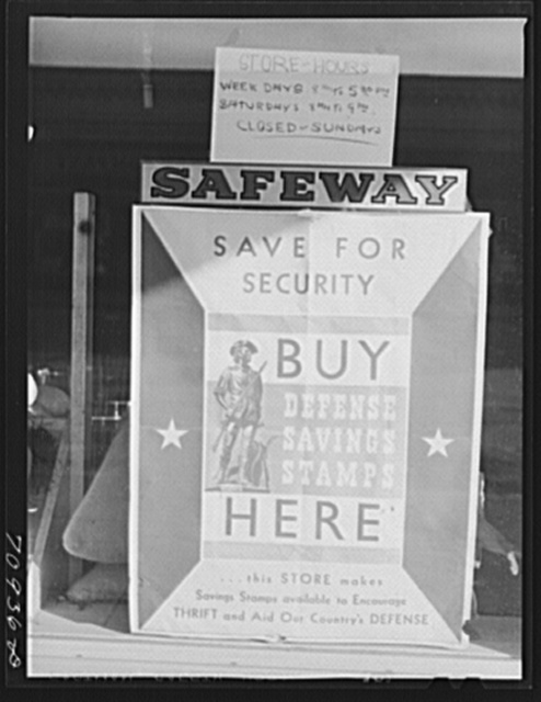 Defense saving stamps sign on grocery store. Payette, Idaho