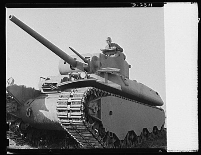 Delivery of the first heavy tanks. This is the new fifty-seven-ton tank, known as the M-1 in the initial demonstration. Notice that the gun turrets are on the top, making it possible for the tank to take advantage of irregular land, sheltering the lower part and shooting from revolving turrets on top. In the turret are three-inch guns and a thirty-seven-millimeter antiaircraft gun