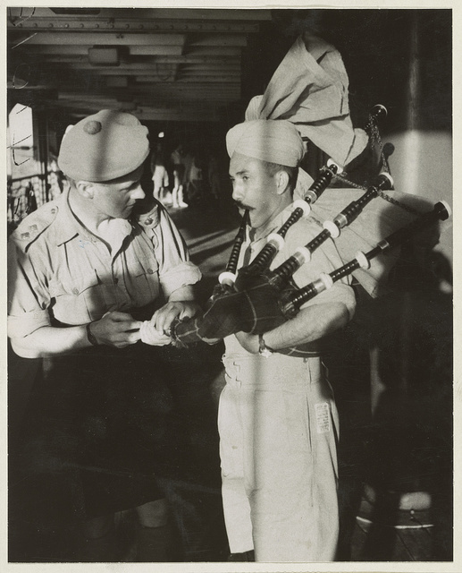 "Diversion on board a troopship bound for the Middle East Picture shows - an Indian officer taking a lesson on the bagpipes (""Presbyterian Whistles"") from a Scots officer."