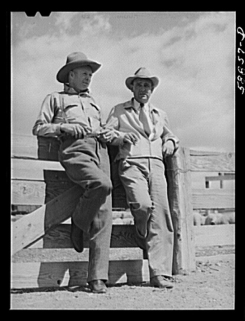"""Doc"" Conway, rancher from Craig, Colorado, talking to Beckman, commission merchant from Denver stockyards, by livestock pens in Craig, Colorado"