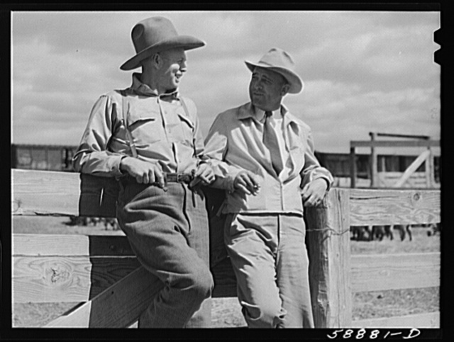 """Doc"" Conway, rancher from Craig, Colorado talking to Beckman, commission merchant from Denver stockyards, by livestock pens in Craig, Colorado"
