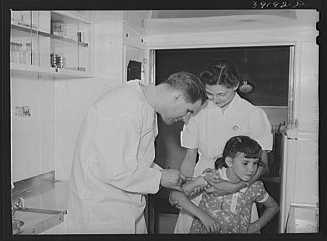 Doctor and nurse with little girl in trailer-clinic at the FSA (Farm Security Administration) migratory labor camp mobile unit. Wilder, Idaho