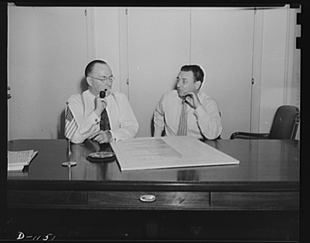 """Donald M. Nelson (left), Chairman, War Production Board (WPB), and Leon Henderson, Administrator, Office of Price Administration (OPA) and Director, Civilian Supply Division of the Office of Production Management (OPM), member of the Supply Priorities and Allocations Board; conferring in Washington, D.C. September 12, 1941. The chart on the table is a distribution and supply chart. While called together for the purpose of having a picture made, Messrs, Henderson and Nelson seized upon the opportunity to have what they termed """"their first real conference in days"""""""