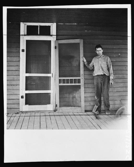 Door assembled in place alongside old door. Screen door construction demonstration. Charles County, La Plata, Maryland