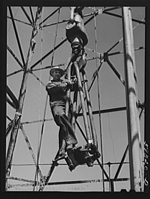 Driller C.L. Saxton, riding on traveling block to the top of oil well derrick. He was originally from Oklahoma, but has been in Kansas for last six years. Oil well in C.C. Graber pool of Continental oil company. Moundridge area near McPherson, Kansas