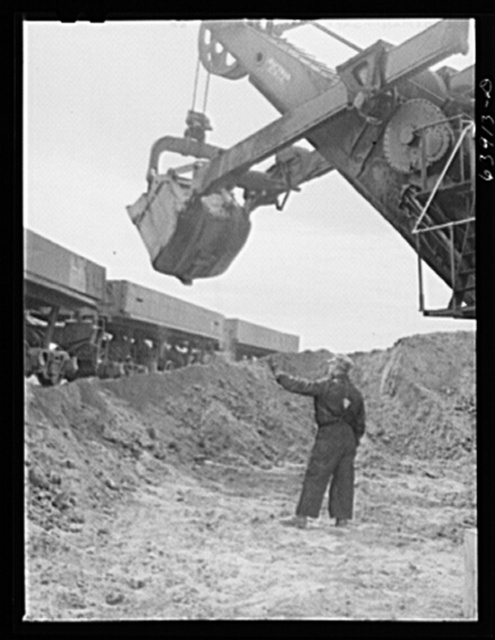 Electric power shovels scoop up iron ore; eight cubic yards per shovelful. Albany Mine near Bovey, Minnesota