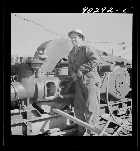 Elmer Womack, derrick man from Fairfax, Oklahoma overhauling mud hog where oil well is being drilled in Goodrich field of Continental oil company. Valley Center oil field near Wichita, Kanasas. He had been working in Kansas fields about six years, used to be a pumper and workerd in oil fields since he was seventeen years old