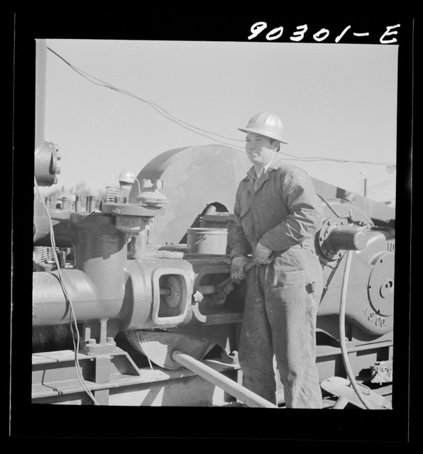 Elmer Womack, derrick man from Fairfax, Oklahoma, overhauling mud hog where oil well is being drilled in Goodrich field of Continental oil company. Valley Center oil field near Witchita, Kansas. He has been working in Kansas fields about six years, used to be a pumper and worked in oil fields since he was seventeen years old