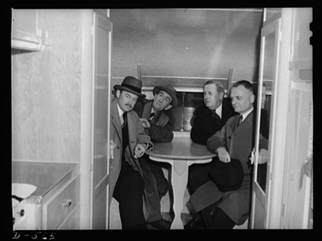 Executives who helped to conceive the trailer idea for relieving overcrowded housing conditions in certain defense areas sit in the dining alcove of a trailer on its way to be put into use in Wilmington, North Carolina. The men are, left to right: Charles F. Palmer, cooridnator of Defense Housing, OEM, Major John Walker, Assistant Administrator, Farm Security Administration; James Cramer, Acting Regional Coordinator for Region 1, Division of Defense Housing Coordination; Carl Bradt, Special Assistant to the Coordinator in Charge of Temporary Shelters, Division of Defense Housing Coordination, Office of Emergency Management