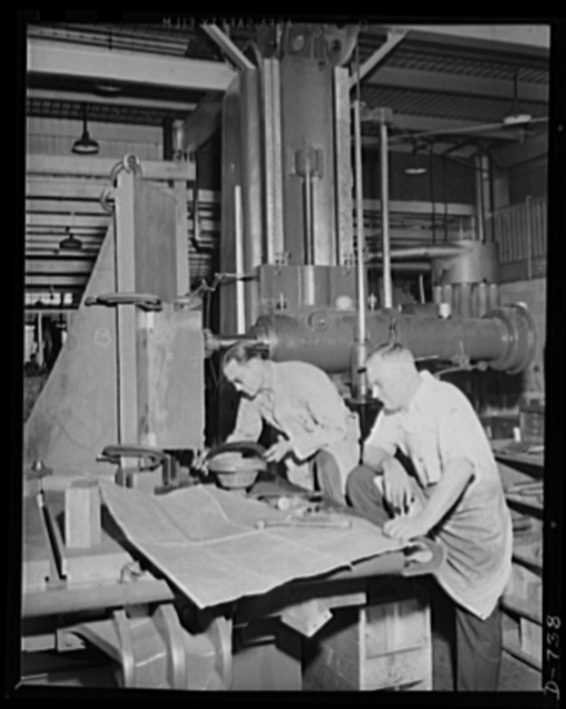 Expert machinists checking a casting which will soon be a part of a machine to make shells. Plant of Frederick Colman & Sons, Inc., Detroit, Michigan