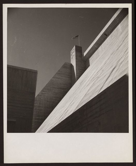 [Exterior wall of dam from below, with flag pole and American flag]