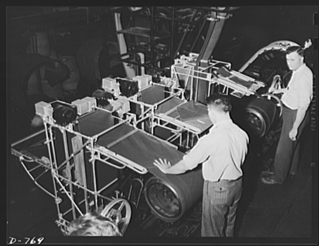 Fabric for automobile tires in the process of manufacture. The fabric here is being wrapped around a collapsible drum. Ford River Rouge plant
