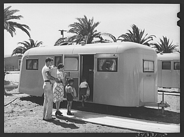 Family moving into trailer at the FSA (Farm Security Administration) camp for defense workers. This family is from Minnesota. The man came to San Diego ten months ago and enrolled in a vocational school. He started to work at Consolidated Aircrafts as a riveter and is now a clerk in the machine shop. Before his family came out three weeks ago he lived in a cabin for which he paid twelve dollars per month. He said it was alright for a man but that he wouldn't take his wife and children into such a place. He got a furnished apartment for his family--it was two rooms, rental eleven dollars per week. His wife soon discovered that there was inadequate hot water and was overrun with roaches and rats. San Diego, California