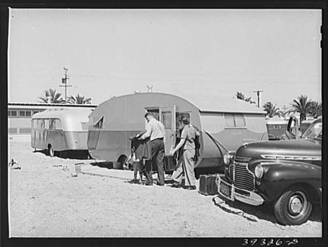 Family moving into trailer at the FSA (Farm Security Administration) camp for defense workers. Before moving to the FSA camp this man had driven fifty-three miles each way daily to work. San Diego, California