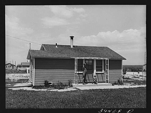 "Farm worker and his young son on porch of their cottage at the FSA (Farm Security Administration) labor camp. Caldwell, Idaho. This man is one of the ""permanent"" farm workers living in the cottages"