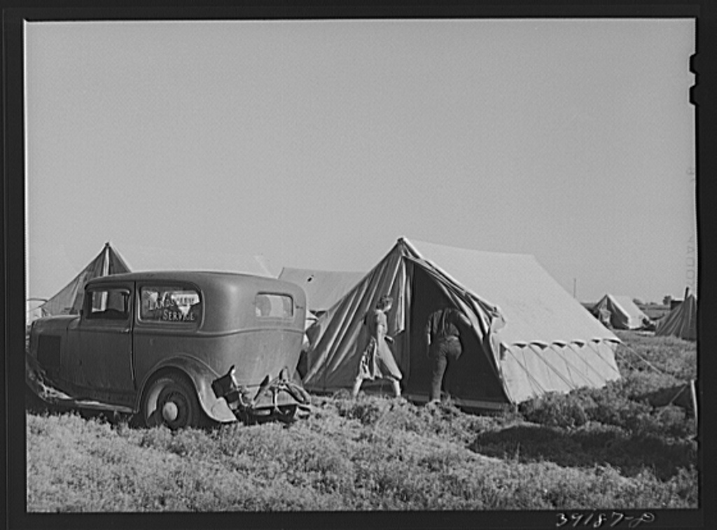 Farm workers unloading their car and moving into tent in which they will live at the FSA (Farm Security Administration) migratory labor camp mobile unit. Wilder, Idaho. Tents are floored. The fact that sanitary facilities are available, hot and cold running water for bathing and laundry work, showers and laundry tubs, community building for entertainment and a trailer clinic are a part of the camp make it a better place to live than perhaps the tents would indicate