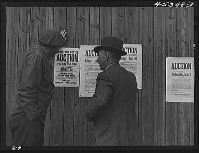 Farmers reading auction notices of farms in the Pine Camp expansion area at an auction of the Ingalls farm near Antwerp, New York