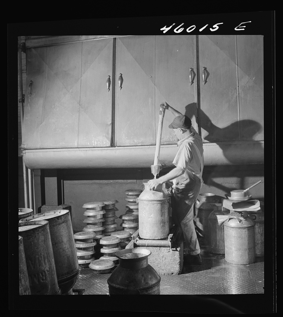 Filling milk cans with cream as it flows from the cooling unit, at the United Farmers' Cooperative Creamery, Sheldon Springs, Vermont