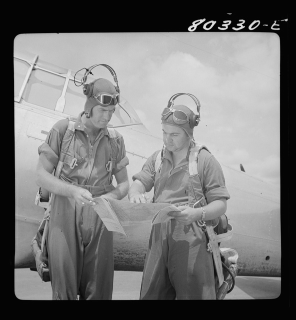 Flight instructors E.E. McTaggart and J.C. Gumison chart the day's flight. Craig Field, Southeastern Air Training Center, Selma, Alabama