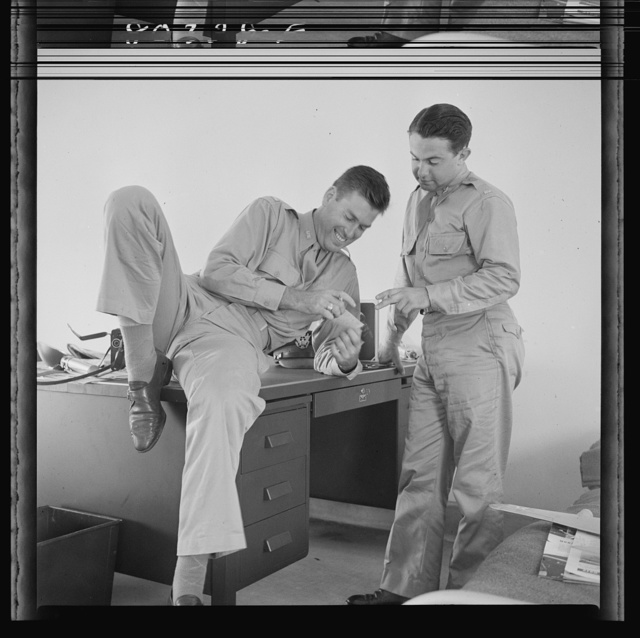 "Flight instructors E.E. McTaggart and J.C. Peresich have a good laugh after a relaxing dinner of FSA (Farm Security Administration) ""Food for Defense"" chickens. Craig Field, Southeastern Air Training Center, Selma, Alabama"