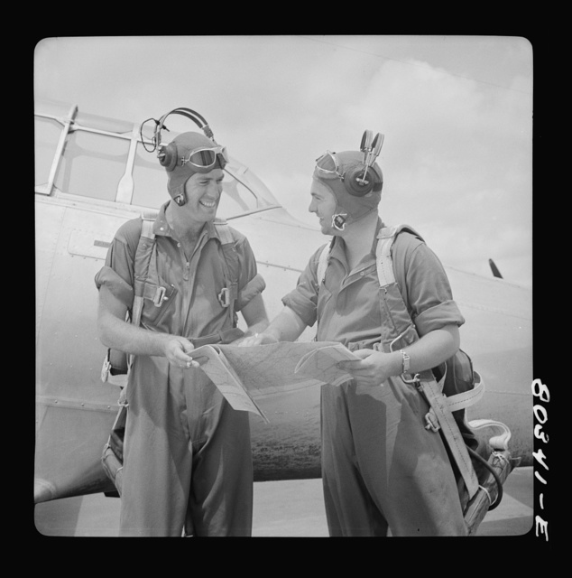 Flight instructors McTaggart and Gumison chart the afternoon flight after fried chicken dinner. Craig Field, Southeastern Air Training Center, Selma, Alabama