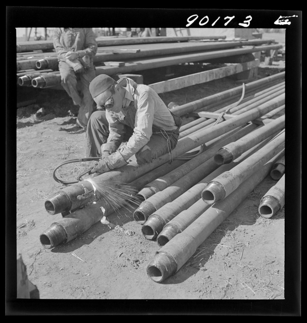 Floyd Swick, welder from Newton, Kansas worked in oil fields about ten years; cutting tool joints off a drill pipe in Goodrich field of Continental oil company. Valley Center oil field near Wichita, Kansas