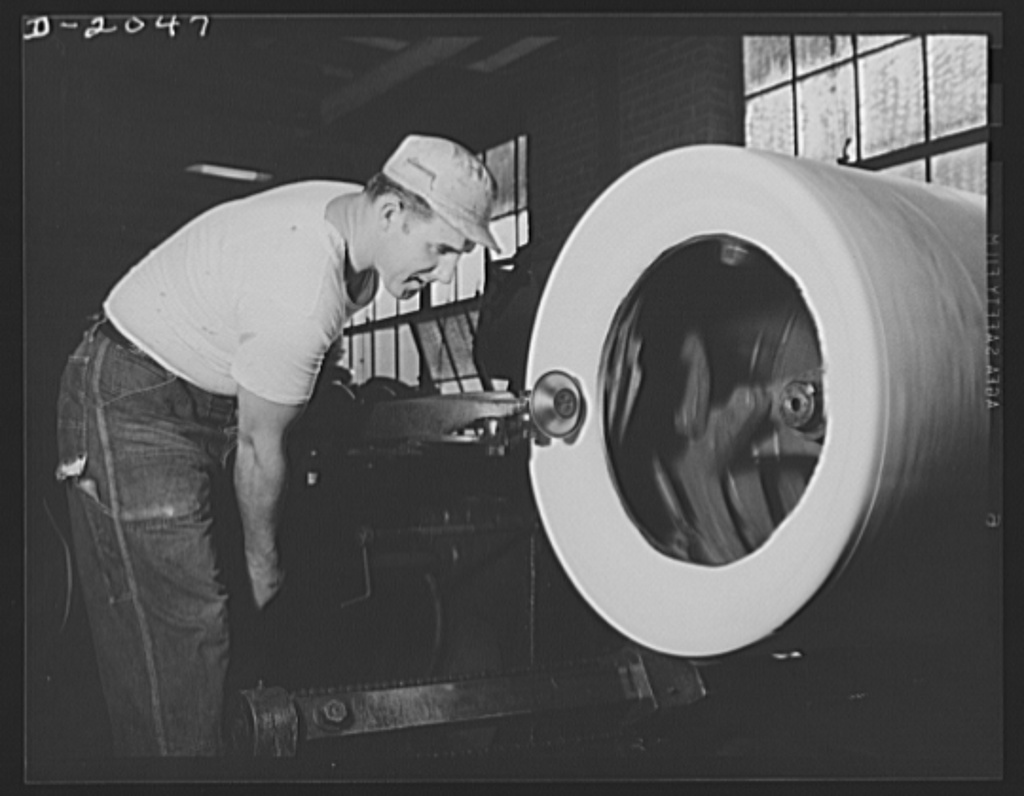 """Forming the bead with """"saucer,"""" this tire builder follows every curve of the tire, shaping and pressing on the new layer. This saucer is matched by another on the far side of the tire which works on the other side at the same time, assuring perfect balance of the finished tire. The saucers may be swiveled in every direction to press the tire at right angles or lightly at a tangent. Firestone (General Tires), Akron, Ohio"""