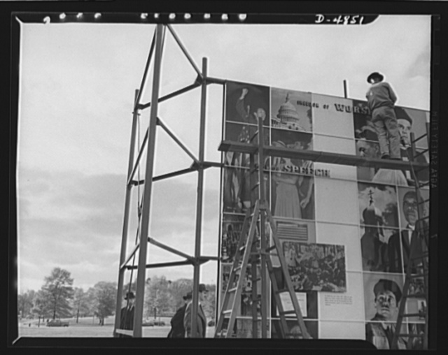 Four Freedoms and Arsenal of Democracy posters. Assembly workers have nearly finished setting up the huge 15 x 30 foot photomontage The Four Freedoms. On the other side of the scaffolding was the Arsenal of Democracy panel, equal in size. The two were displayed in Defense Square, Washington for a month beginning November 7, 1941. Designed for the Office of Emergency Management (OEM) by the eminent poster artist Jean Carlu, they were shown first in New York and after the Washington showing went on a tour of many cities throughout the nation