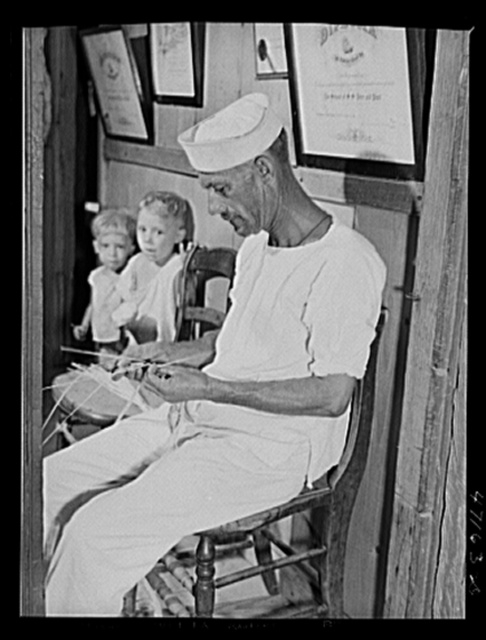 French village, a small settlement on Saint Thomas Island, Virgin Islands. A seaman who makes extra money weaving straw objects which are sold at the handicrafts cooperative