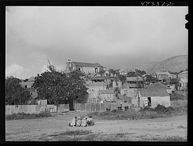 French village, a small settlement on Saint Thomas Island, Virgin Islands. Children playing marbles. The Catholic church on the hilltop