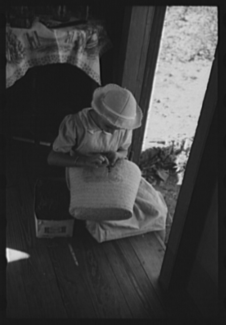 French Village, a small settlement on St. Thomas Island, Virgin Islands. Young girl embroidering a straw basket to be sold in the handicrafts cooperative in Charlotte Amalie