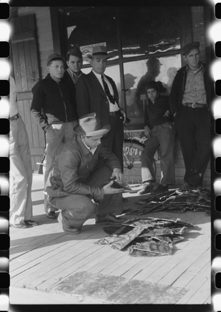 Grading muskrats while fur buyers and Spanish trappers look on, during auction sale on porch of community store in St. Bernard, Louisiana