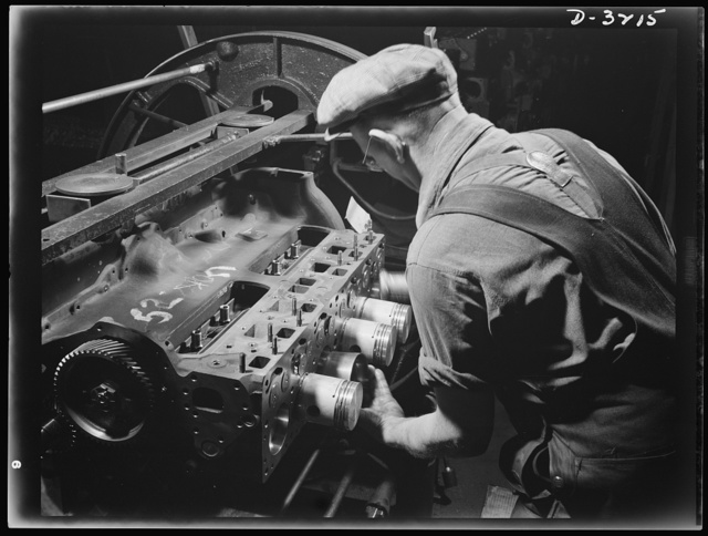 Halftrac scout cars. Putting precision-made pistons assemblies into precision-made cylinders is a job that fits this former auto worker. The engine will be the power plant of an Army halftrac scout car. The Midwest plant that is turning it out has trained American automotive workers for every job on the line. White Motor Company, Cleveland, Ohio