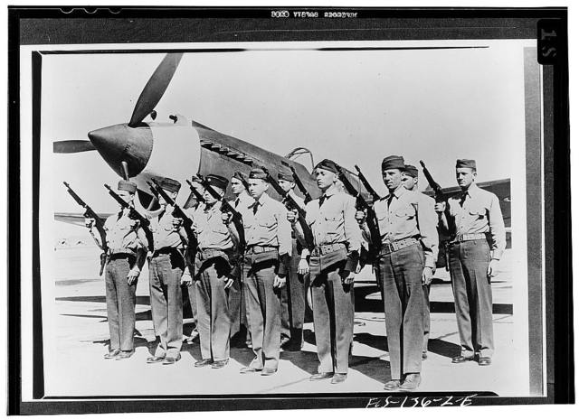 Hamilton Field, California. A security squad lined up in front of a fast pursuit ship and fully equipped with Thompson sub-machine guns that will pour out 500 large-caliber slugs a minute
