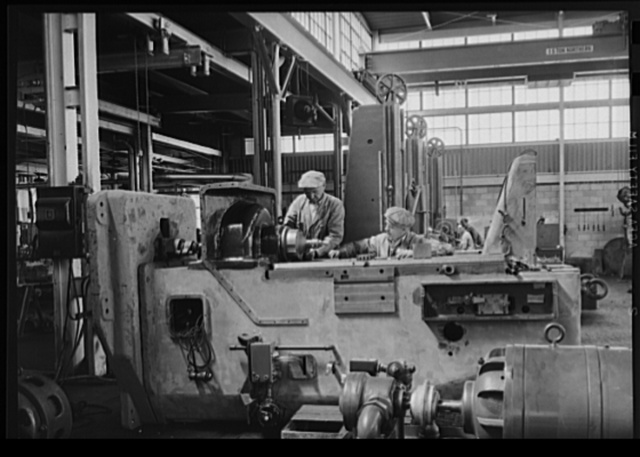 Here is most important tool, a machine built to turn 105 mm shells. Workmen here are checking the spindle lineup before the machine is shipped. Photo made at Frederick Colman & Sons, Inc., tool and die makers, Detroit, Michigan