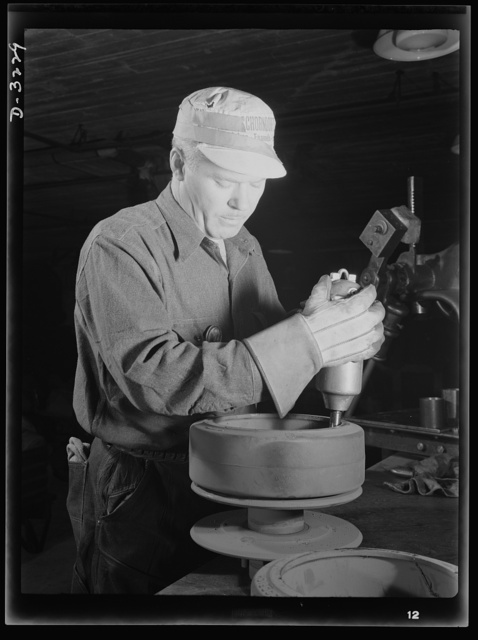 He's preparing rollers for a bogy assembly for a halftrac scout car produced, with many more like it, by a Midwest truck manufacturer. White Motor Company, Cleveland, Ohio