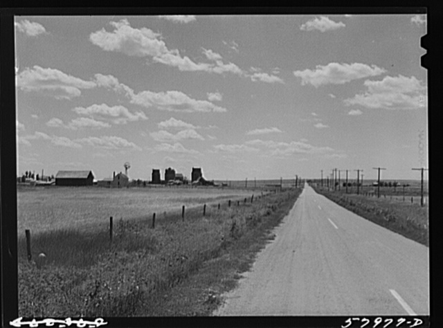 Highway, showing grain elevators and part of town of Froid, Montana